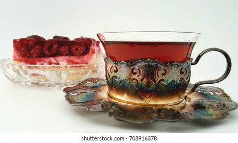 Tea in a decorative glass and a piece of cake with raspberries.