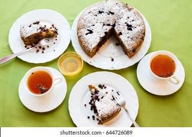 Tea drinking. Homemade cake on a white plate on green and orange colored fabrics