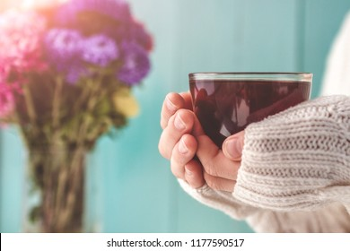 Tea drinking. A woman in a white, knitted pullover is holding a cup of hot tea in her hands. Cozy pastime. Autumn, winter drinks.