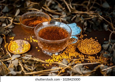 Tea of fenugreek/Fenugreek tea with honey,sugar fenugreek leaves and seeds on a wooden surface with dark Gothic colors.Benefits are include relief from anemia, loss of taste, fever, dandruff etc.