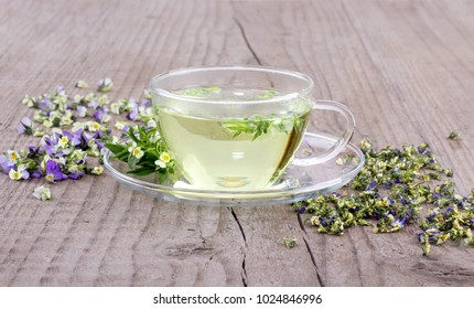 Tea with fresh and dried flowers from field pansy on a wooden background