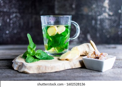 Tea with fresh mint and ginger pieces on a wooden board. Ideal as an eye-catcher.
