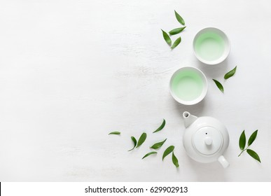 Tea freshly brewed in a teapot and two cups, surrounded with fresh tea leaves, top view composition, space for a text