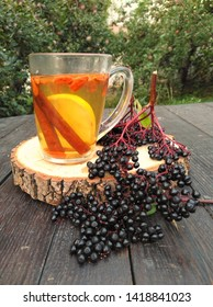 Tea in the garden at the old oak table.  Tea with cinnamon, lemon, goji berries and elderberry on a wooden stand