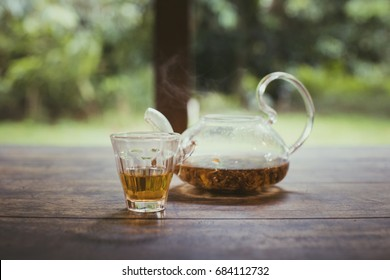Tea in glass with tea being brewed in a glass jug placed on a table and located in the backyard. This image has a retro feel because it uses film tones. Selective focus