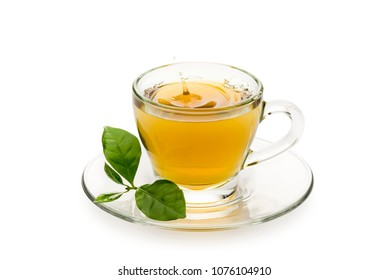 tea in glass cup with leaves and drop splashing, on white background