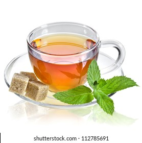 tea in glass cup with mint leaf and brown cane sugar cubes isolated on a white background