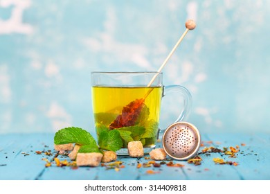 tea in glass cup with mint leaf and brown cane sugar on a blue wooden board