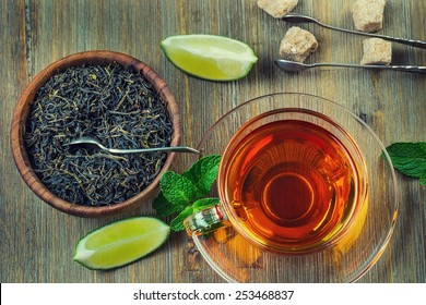 Tea in a glass cup, mint leaves, dried tea, sliced lime, cane brown sugar