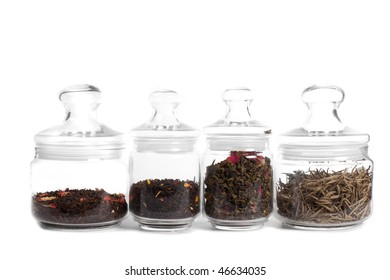 Tea in glass jars: (from left to right) milk puer, aromatized indian tea, oolong with rose, white tea (silver needles) isolated on white.