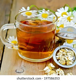 Tea in glass mug, metal sieve with dry chamomile, a bouquet of fresh flowers daisies on a background of wooden boards