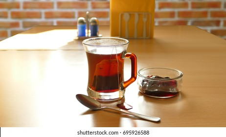 Tea in a glass on a brick background toned image