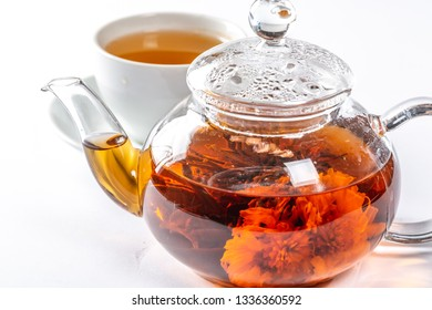 Tea in a glass teapot with a blooming large flower. Teapot with exotic green tea-balls blooms flower. Tea ceremony