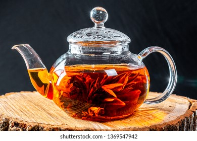 Tea in a glass teapot with a blooming large flower. Teapot with exotic green tea-balls blooms flower. Tea ceremony on a wooden stump