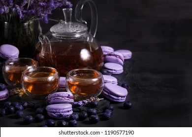 Tea in the glass teapot with lavender and blueberry macarons. Copyspace background.