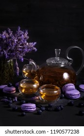 Tea in the glass teapot with lavender and blueberry macarons