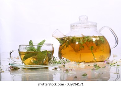 Tea from grasses and mint in a transparent teapot and a cup on a white background