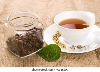 Tea, green leaf and glass coffee jar with burlap background