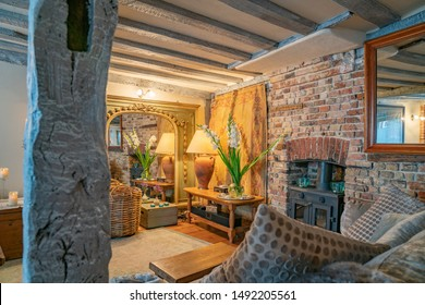 The Tea House Lounge room rustic support and ceiling beams  brick wall and golden hue lighting reflected in mirror Rye United Kingdom.