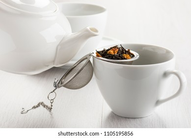 tea infuser opened on white cup with herbal mixture for tea.