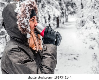 Tea keeps girl warm outside. Young woman enjoying hot drink in winter. Spruce Tree Forest Covered by Snow in Winter Landscape on the background . image for wallpaper. Copy space