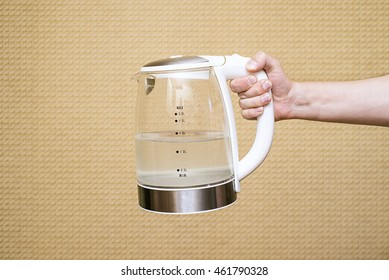 Tea kettle with boiling water in the kitchen close up, men hand hold the glass electric kettle, preparing hot drink