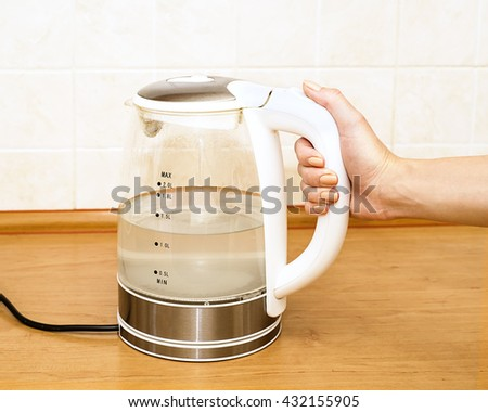 Tea kettle with boiling water in the kitchen close up,  Woman hand hold the glass electric kettle, preparing hot drink