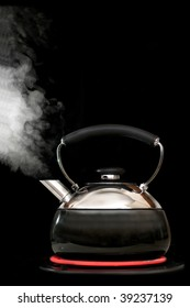 Tea kettle with boiling water on black background. Heater glow under the kettle.