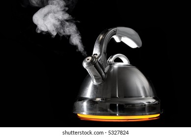 Tea kettle with boiling water on black background. Heater glow under the tea kettle.
