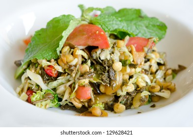 Tea Leaf Salad (Pickled green tea leaves, cherry tomatoes, cabbage, fresh lime, fried garlic, sesames seed, and roasted nuts)