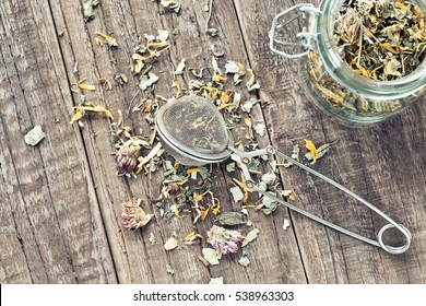 Tea leaves with a tea strainer and a glass on a wooden table