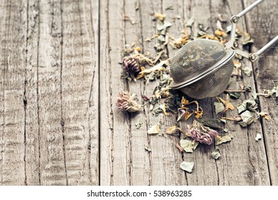 Tea leaves with a tea strainer on a wooden table