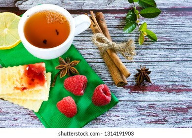 tea with lemon raspberries and jam, top view on a textured background