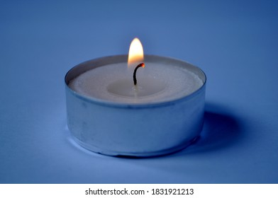 Tea light candle burning dark background