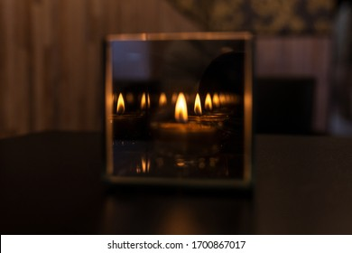Tea light, candle is mirrored in cubic glass cup