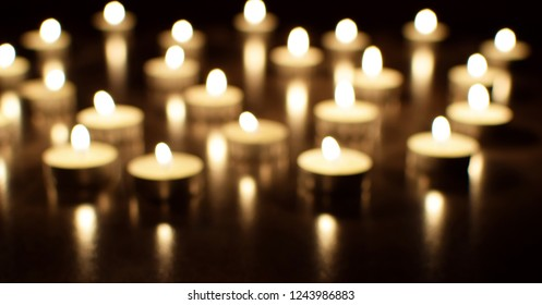 Tea light candles burning in darkness. Advent or memorial prayer candle flame.