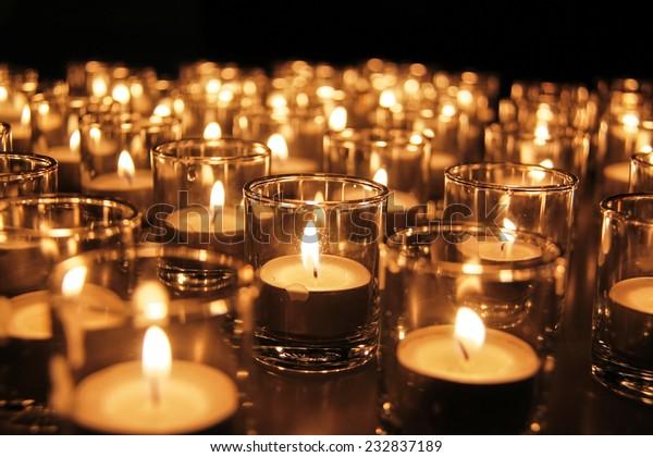 Tea lights in glass jar illuminates a dark surrounding
