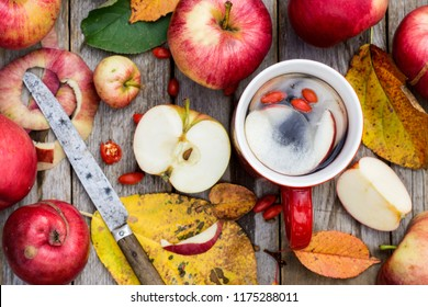Tea made of  apples and goji berries on a wooden grey table; food and drink concept