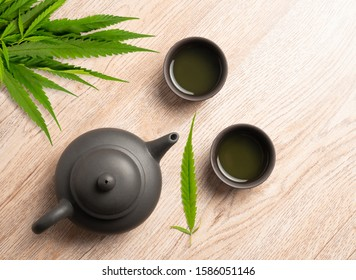 Tea made from cannabis leaves ,A glass of hot marijuana tea on wooden table , tea pot and cups on wooden table ,
