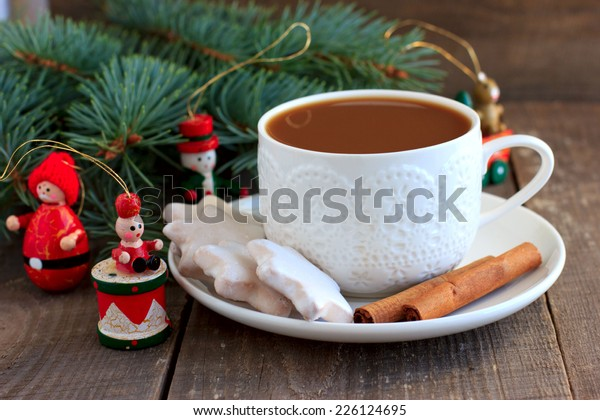Tea with milk and cinnamon in white cup and Christmas decor