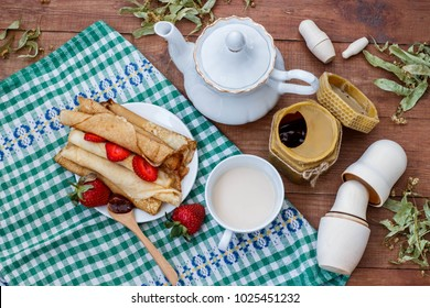 tea with milk, pancakes, honey and strawberries on a wooden brown table