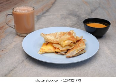 Tea with milk, Roti canai or Roti Parata and curry sauce on the plate over wooden  table