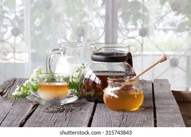Tea with milk in a transparent cup with honey, on a wooden table