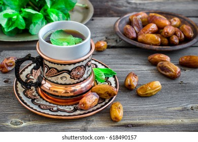 Tea with mint in arab style and dates on wooden table. Selective focus.