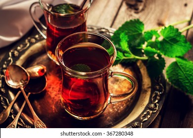 Tea with mint in the Arab style on wooden table. Selective focus. Instagram effect.