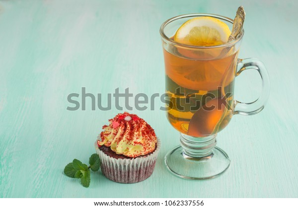 Tea with mint and lemon and cake on a light background.