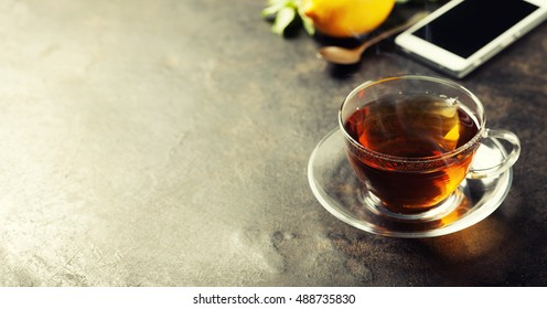 tea and mobile phone on dark rustic background