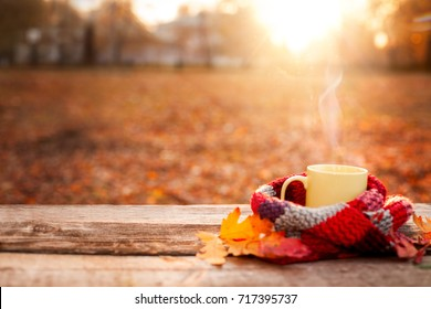 Tea mug covered with warm scarf on wooden surface with red leaves