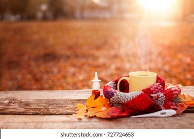 Tea mug covered with warm scarf, thermometer and nose drops on wooden surface with red leaves