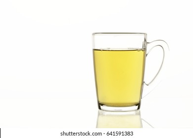 Tea mug with green tea on white isolated background, glass dish for liquids concept